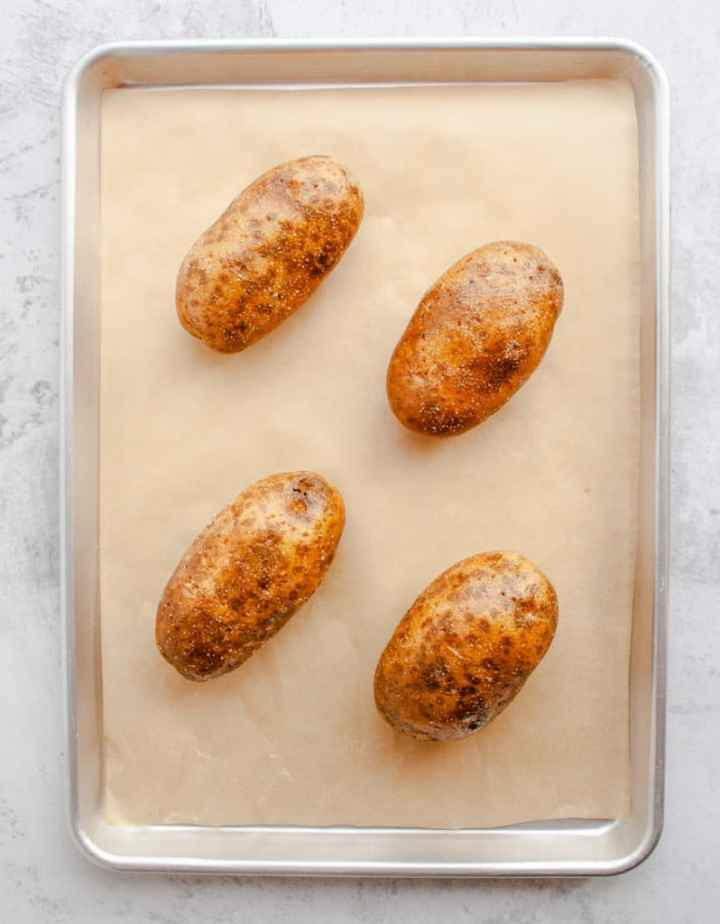 Russet Potatoes on a parchment lined baking sheet ready for the oven