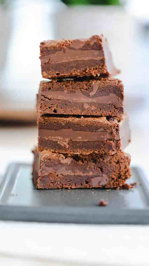Stack of three brownies sit on grey serving platter advertising a brownie recipe for Best Fudgy Chocolate Bar Brownies.