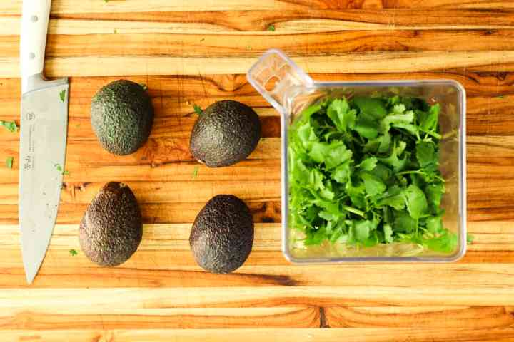 Four ripe avocados sit on a wooden cutting board ready to be sliced and added into blender full of bright green cilantro.