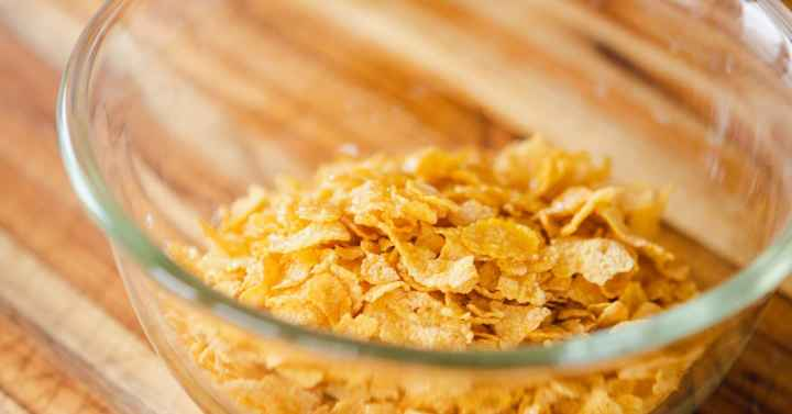 Glass bowl of crispy Kellog's cornflakes sitting on wooden cutting board ready to be placed on top of the casserole.