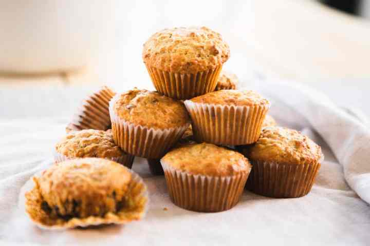 Bran muffins in paper liners sit stacked in a tower, on top of a white towel.