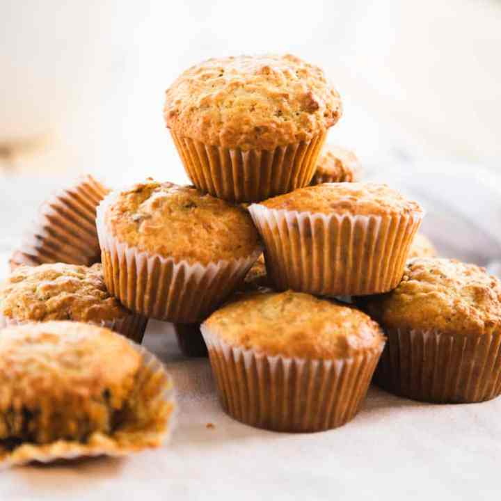 Nine bran muffins sit stacked on a surface ready to eat.