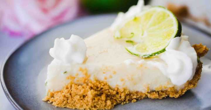 Slice of Key Lime Pie with graham cracker crust on a plate. Soft pink rose sitting in background.