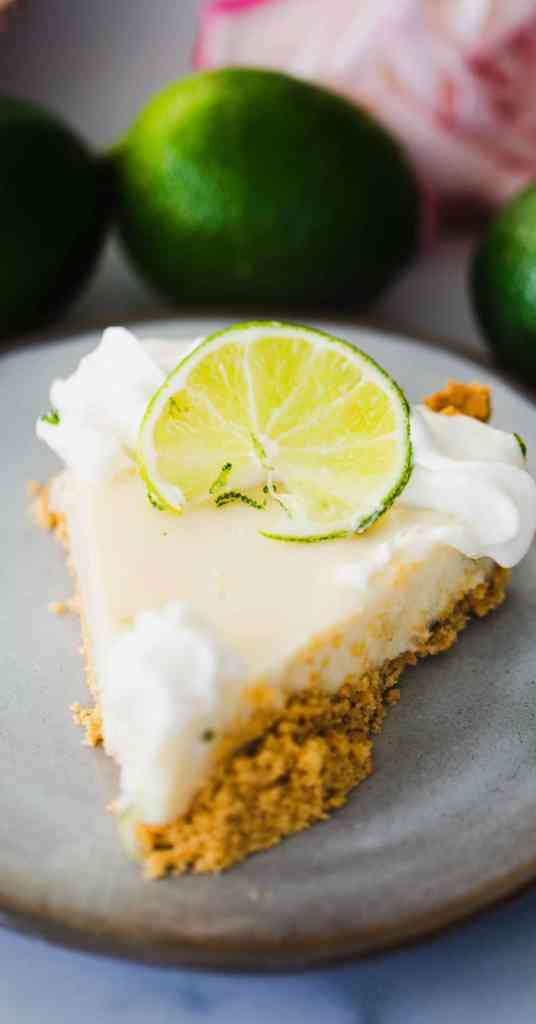 Slice of tender key lime pie on a plate ready to eat.  Key lime pie is decorated with whipped topping and lime slice.