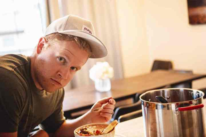 Dallin leans over the counter with a bowl of chili, spoon in hand, ready to take a bite.