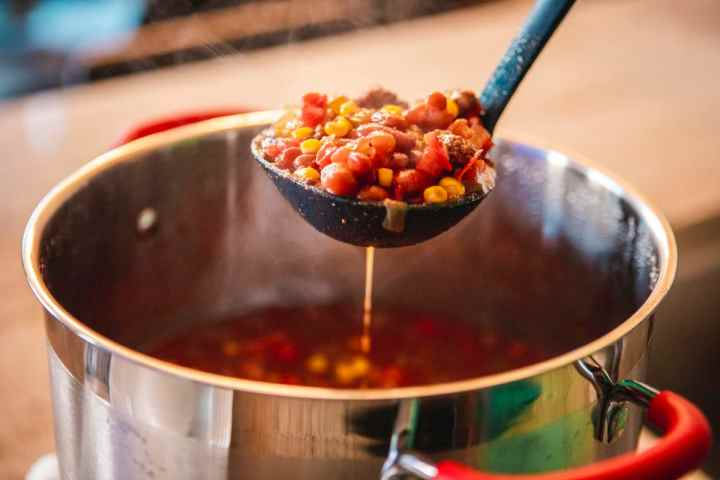 Large pot filled with sweet and spicy chili sits on the counter. A ladle full of sweet and spicy chili sits ready to serve.