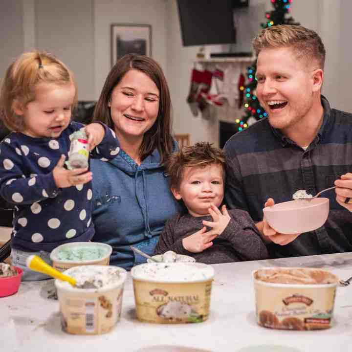 James, Ashley, George and Dallin sit at the kitchen counter behind four cartons of icecream. Bowls of scooped ice cream surround them. James is eating sprinkles out of the container.