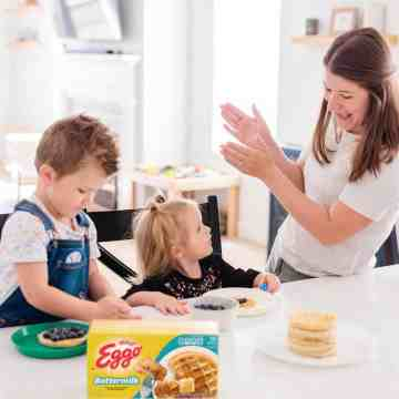 George and James sit at the counter with plates of eggo waffles and blueberries in front of them. Ashley stands next to James smiling and clapping her hands.