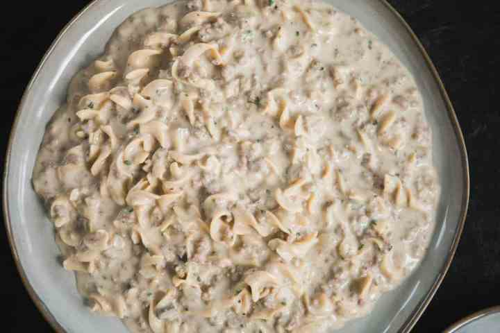 Large plate sits on a black counter. Plate is filled with beef stroganoff, hot and ready to eat. Egg noodles are covered in a meaty cream sauce.