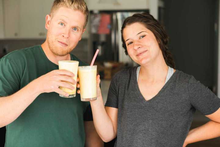 Two people happily drinking an orange julius (serve immediately)