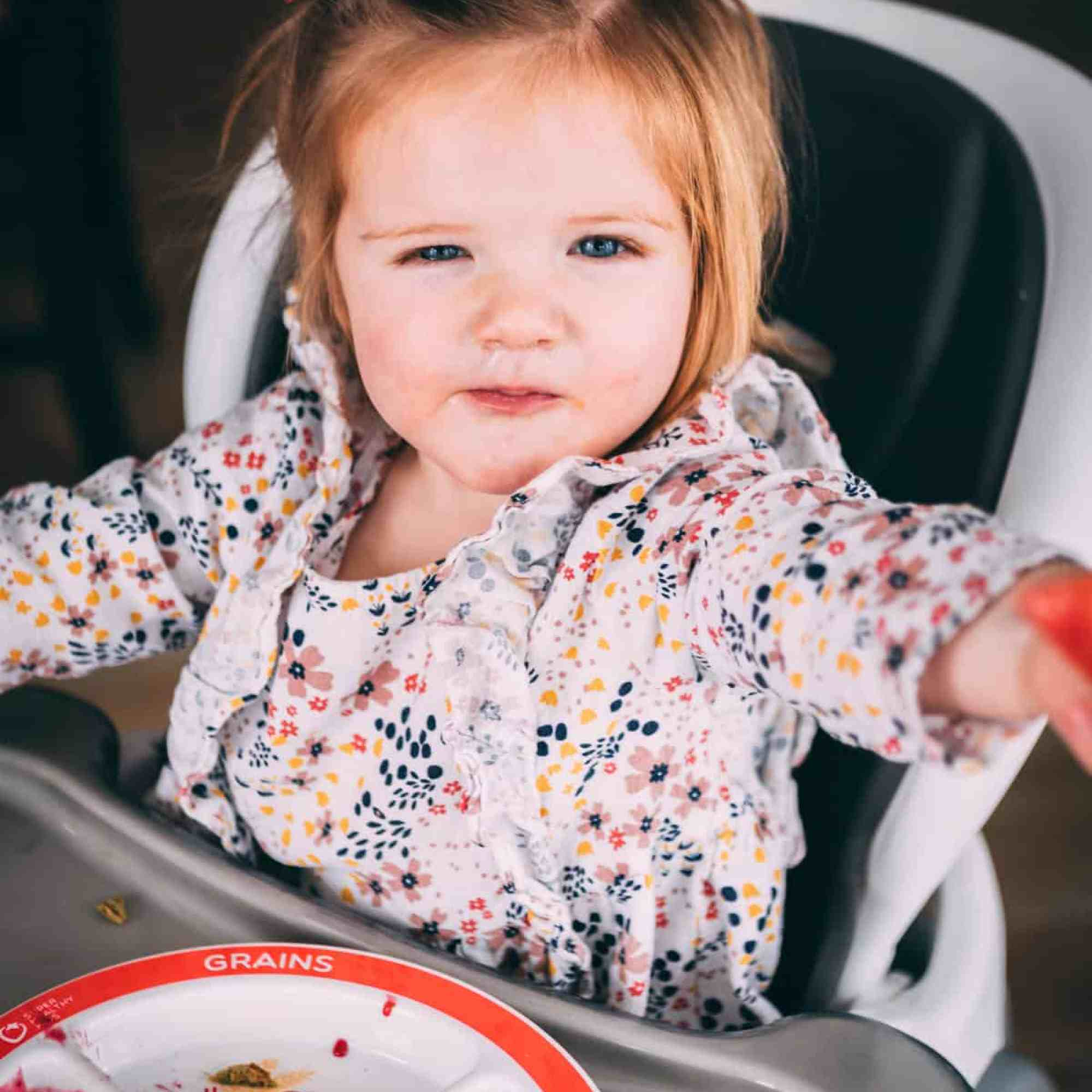 James looks up from her highchair smiling with a plate of waffle in front of her.