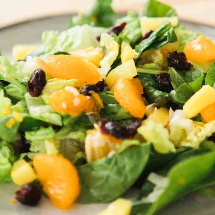 Plate filled with citrus and cranberry winter salad sits on a table.