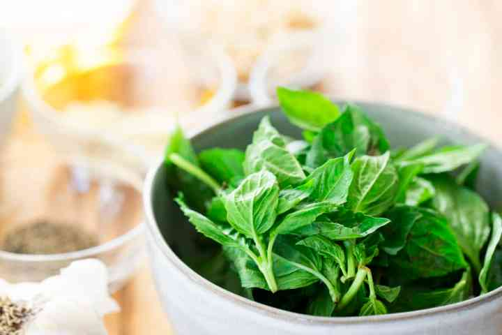 Bowl of fresh ingredients sit alongside a large bowl of basil.