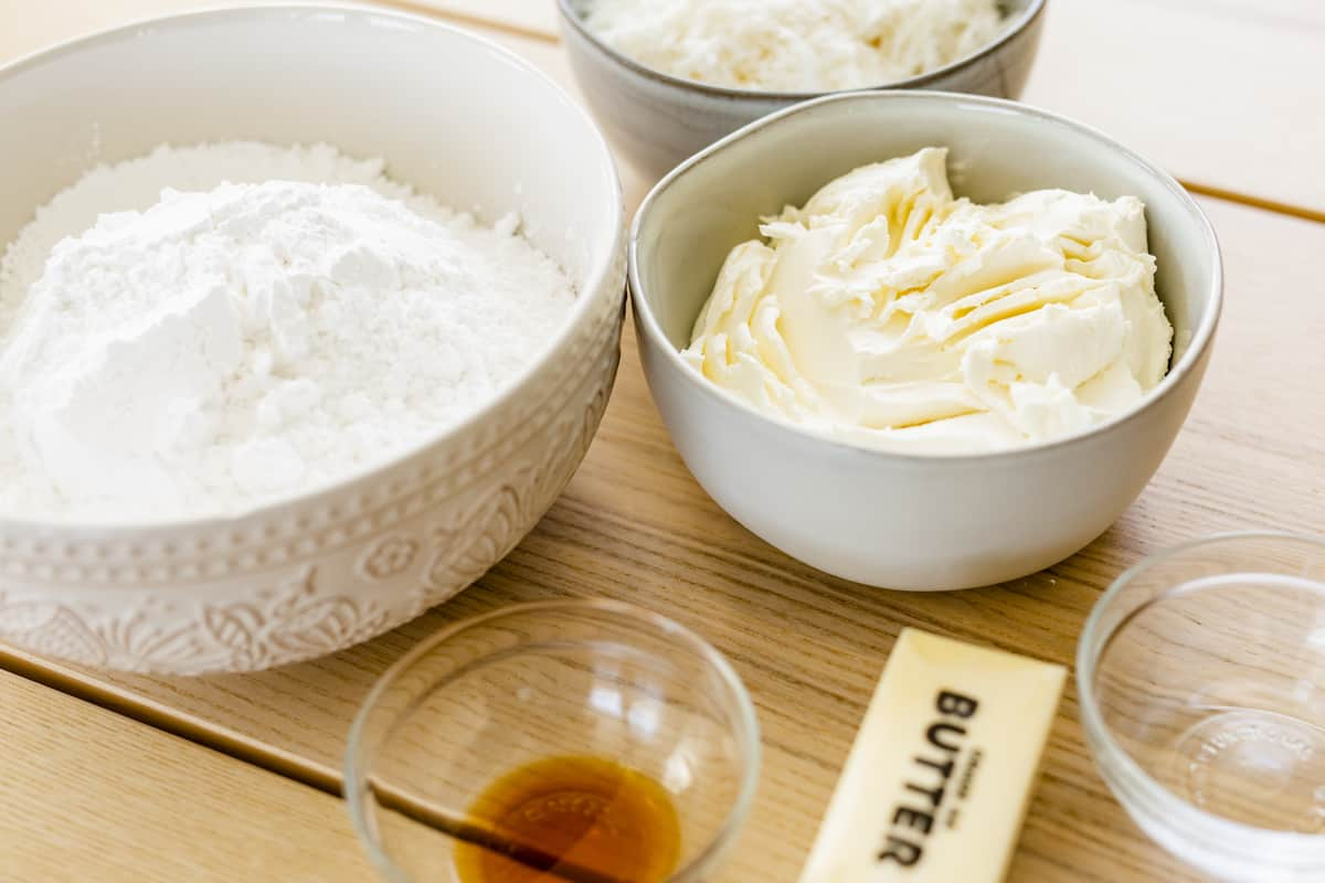 Ingredients for coconut cream cheese frosting sit on a counter top.