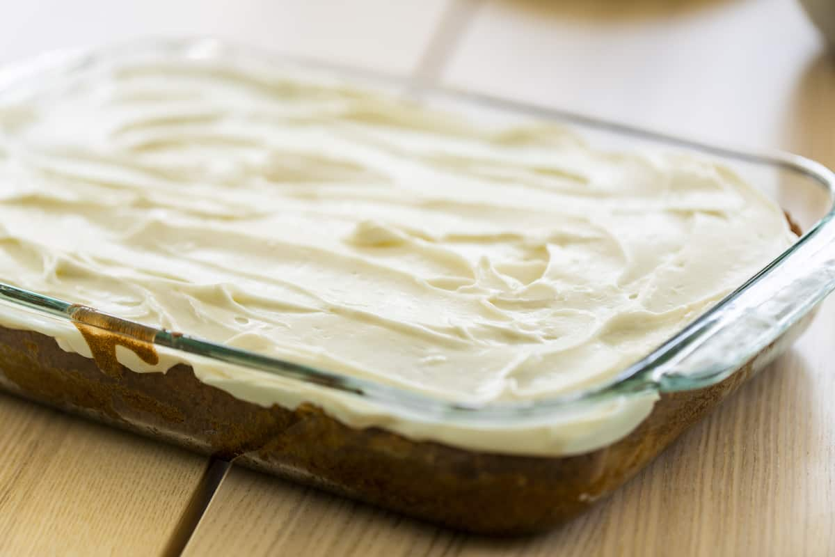 9x13 glass casserole dish sits on the counter filled with banana cake and iced with coconut cream cheese frosting.