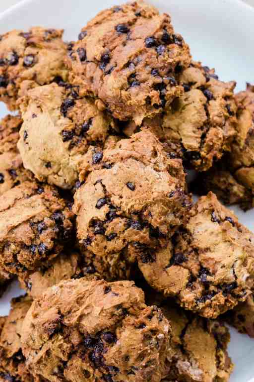 Fresh baked, melt in your mouth pumpkin spice chocolate chip cookies sit on a plate.