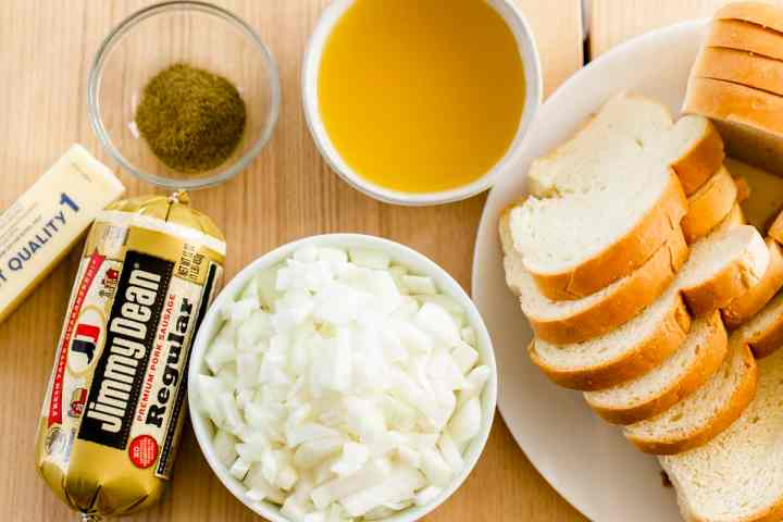 A loaf of bread sits on a plate, diced onions in a bowl, roll of sausage, a stick of butter, vegetable broth in a bowl and Italian seasonings sit on a countertop ready to be used in the recipe.