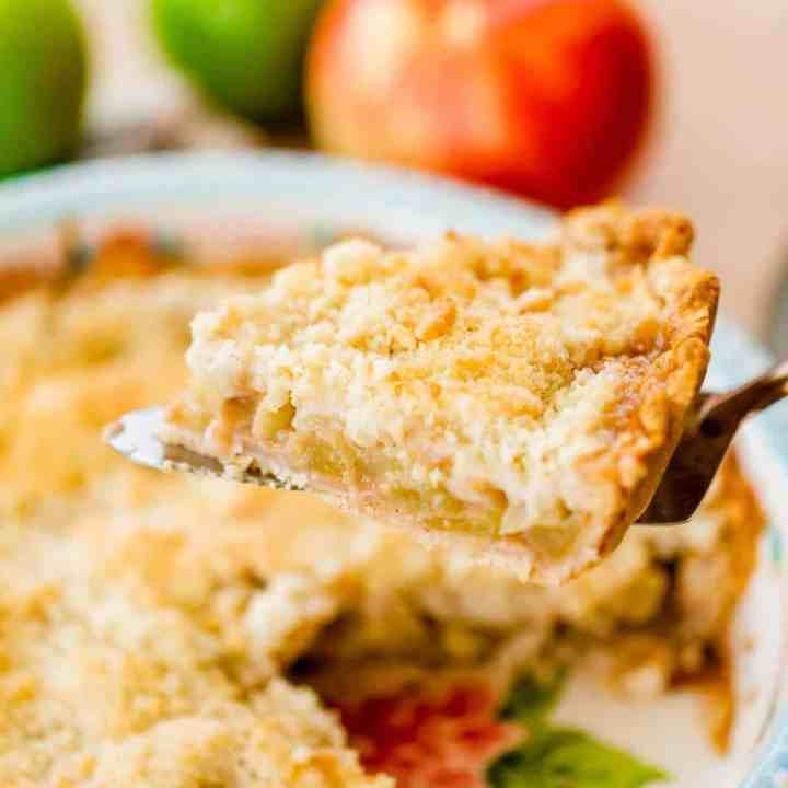 A slice of Dutch Apple pie sits on a pie serving spatula ready to move to a plate.