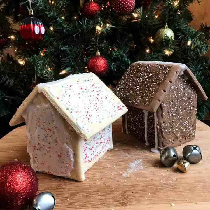 Two pop tart houses sit in front of a lit Christmas tree ready for decorations. Jingle Bells surround the houses.