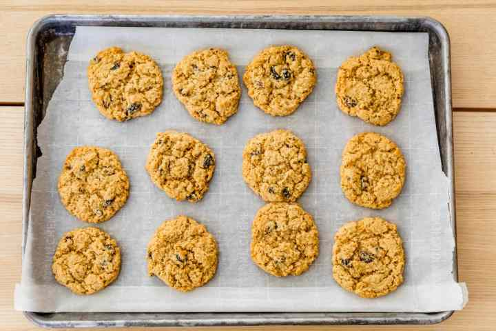 12 Sunshine cookies sit cooling on top of parchment paper on a weathered cookie sheet.