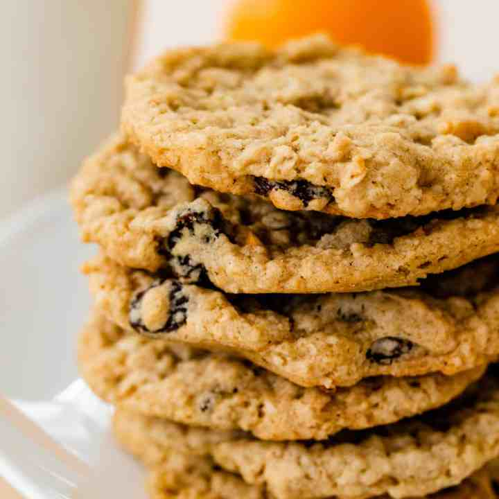 Six freshly baked cookies loaded with orange zest and raisins sit on top of each other on a white platter.