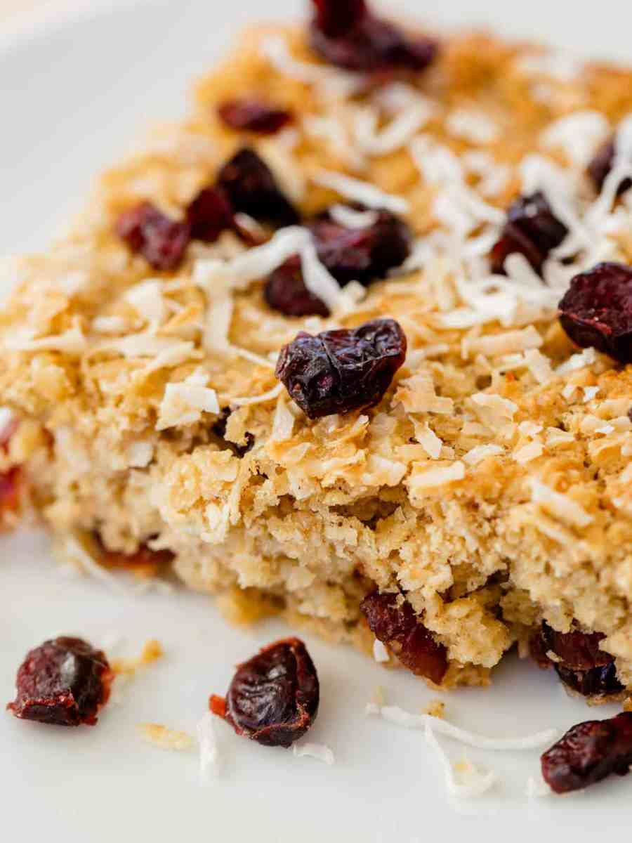 Breakfast bar sits on a plate with extra craisins and shredded coconut.