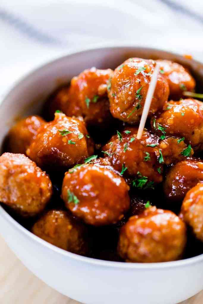 Bowl full of hot meatballs covered in sticky honey garlic glaze is ready to enjoy. A toothpick sits in a meatball in the center of the bowl.