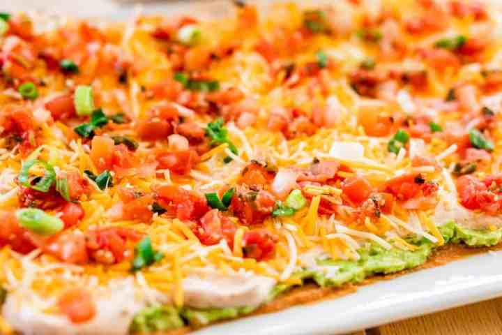 Best seven layer Mexican dip sits on a platter ready to be scooped up and enjoyed.
