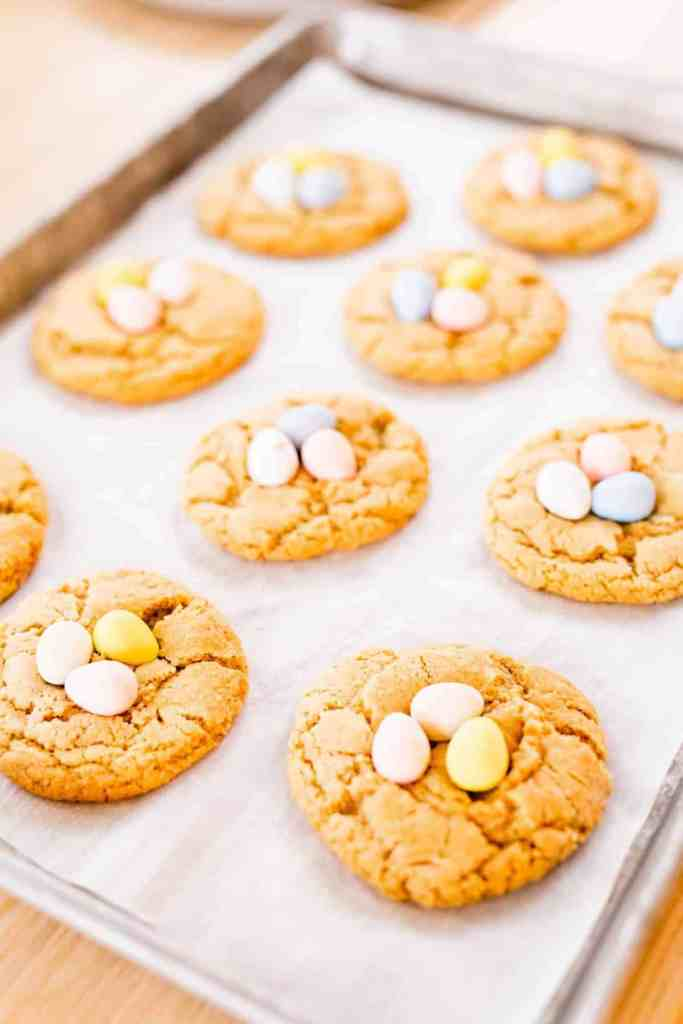 Cookies on the baking sheet have each been topped with 3 Cadbury mini eggs.