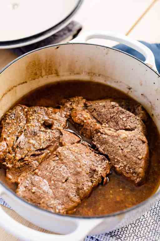 A cast iron pot sits on the stove with a perfectly cooked chuck roast sitting in au jus.