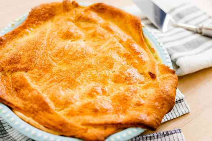 A golden brown chicken pot pie has been pulled from the oven and is resting on the table top ready to serve.