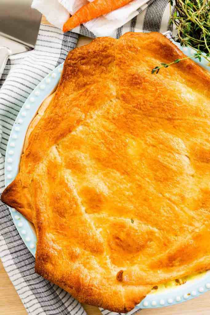 A beautiful golden brown Chicken Pot Pie in a pie dish is ready to slice and serve.