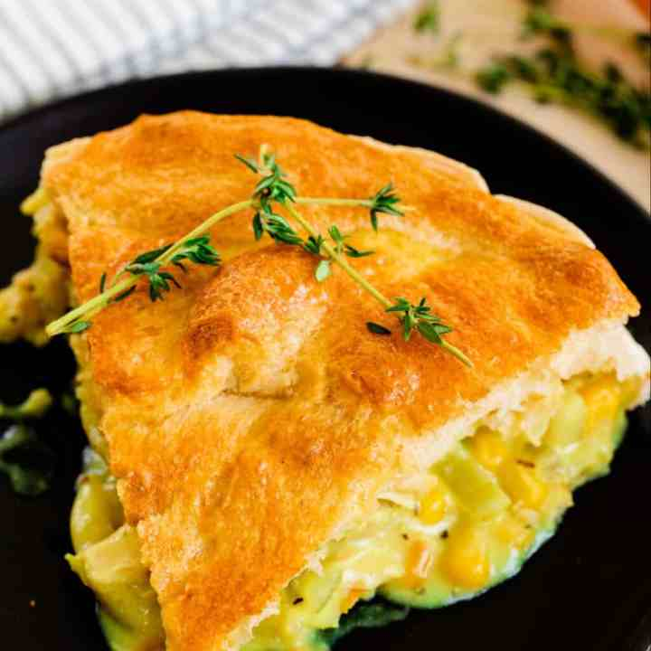 A generous slice of pot pie sits on a plate, ready to be eaten.