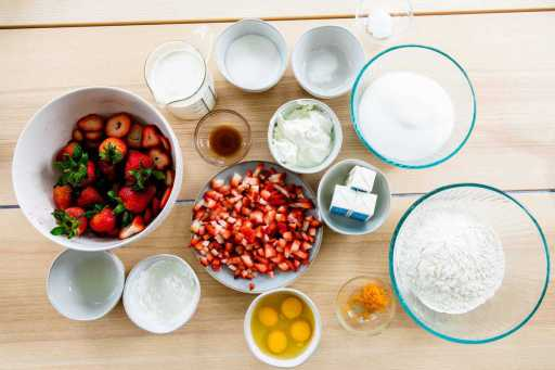 Ingredients for strawberry cake sit on a table top in small individual bowls.