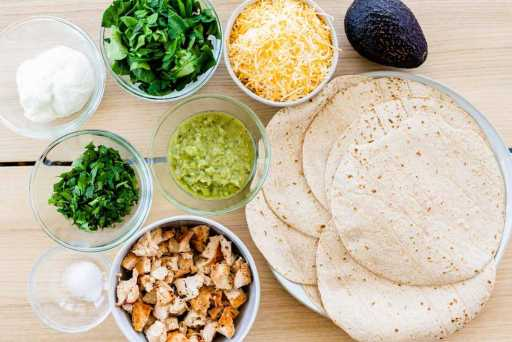Ingredients for green machine quesadilla sit on the counter top in small glass and ceramic bowls. Cilantro, spinach, sour cream, salsa verde, grilled chicken, avocado, salt, cheese and tortillas.