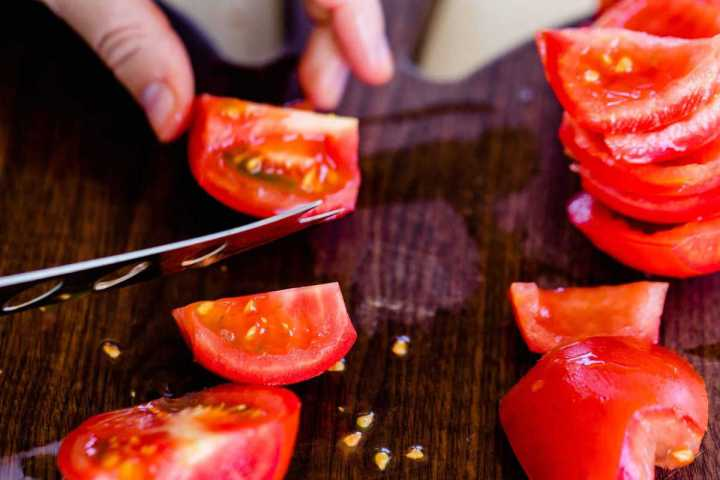 Ashley holds a knife while she removes the center of red plump tomatoes.