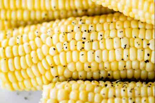 Cooked corn on the cob sits stacked on a white plate sprinkled with pepper, ready to eat.