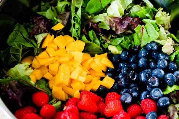 Bright, vibrant mangoes, raspberries and blueberries sit on top of a bowl full of dark mixed greens.