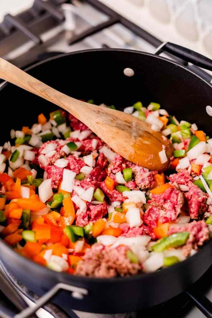 Ground beef, chopped onions, peppers and beans are stirred in a large black pot as they simmer and cook.