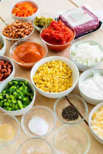 Ingredients for tamale pie filling sit on counter in small bowls ready to be added to a pot for cooking.