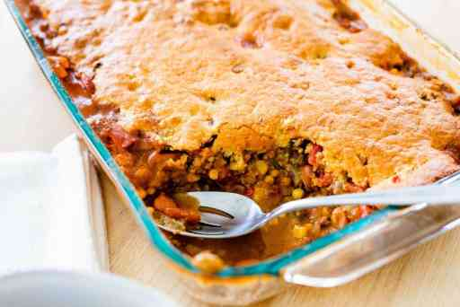 Casserole dish full of tamale pie sits ready to serve with silver slotted spoon.