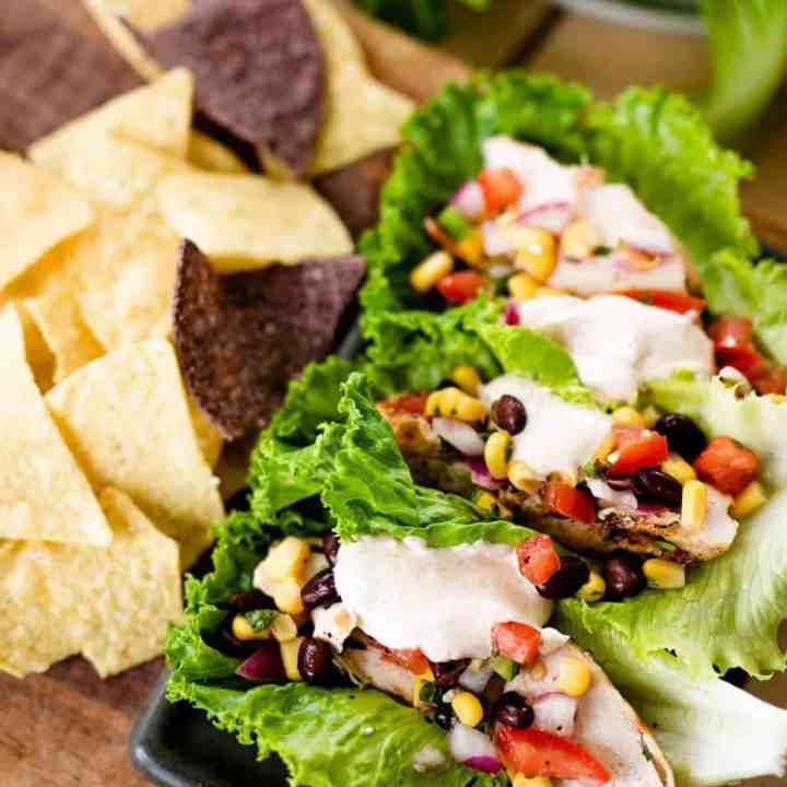 Southwest wraps sit on a plate beside crisp tortilla chips ready to enjoy.