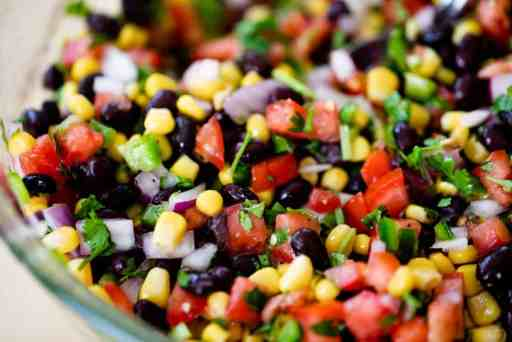 A large glass bowl is filled with Cowboy Caviar ready to serve.