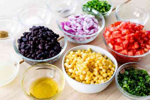 All the ingredients for Cowboy Caviar sit in small bowls on a wooden countertop ready to be mixed together.
