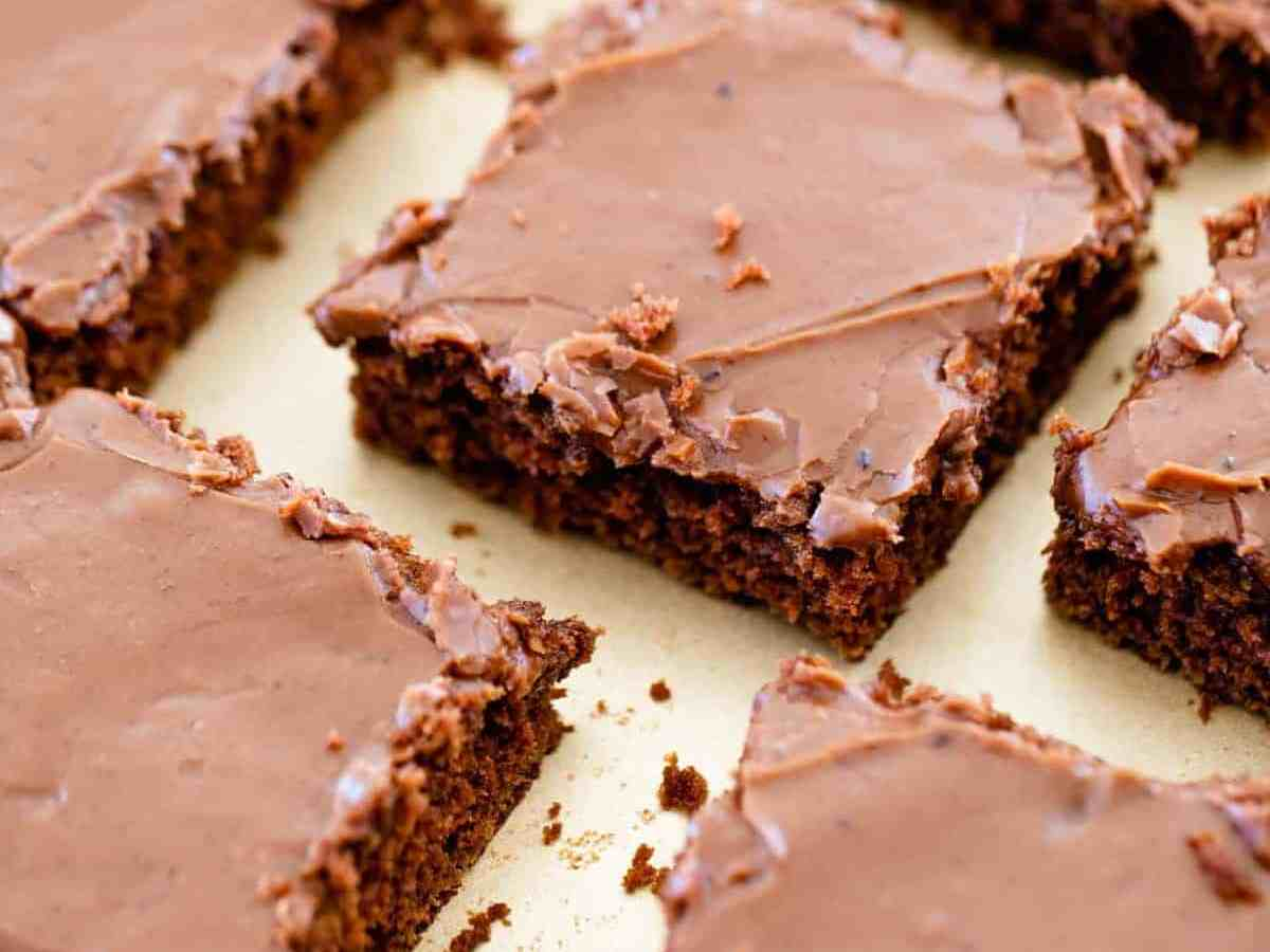 Cake is sliced into squares and sits on a sheet pan ready to serve.