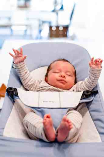 Baby violet sits on the counter in a bouncer with eyes closed and both hands raised in the air.