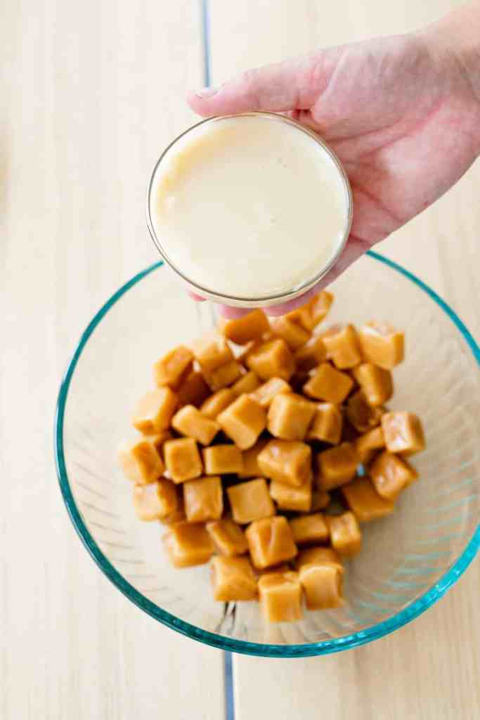 Unwrapped caramel squares sit in a glass bowl while a small bowl of evaporated condensed milk is held over the top.