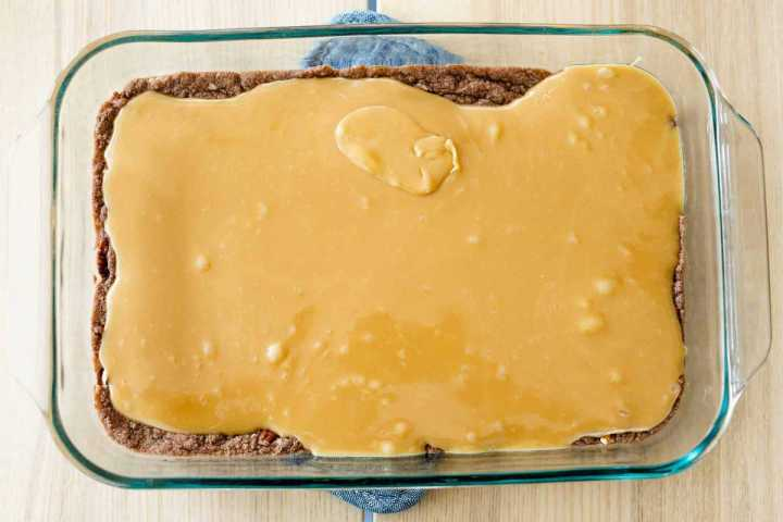 Caramel sauce is poured out and spread over the cooked brownie base layer.
