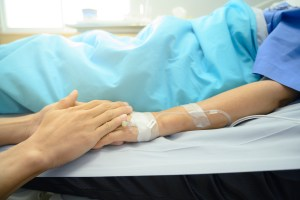 A son holds his mother's hand as she lies in a hospital bed.