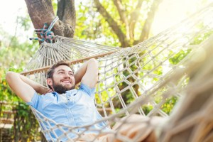A man relaxes in a mesh hammock tied to a large tree.
